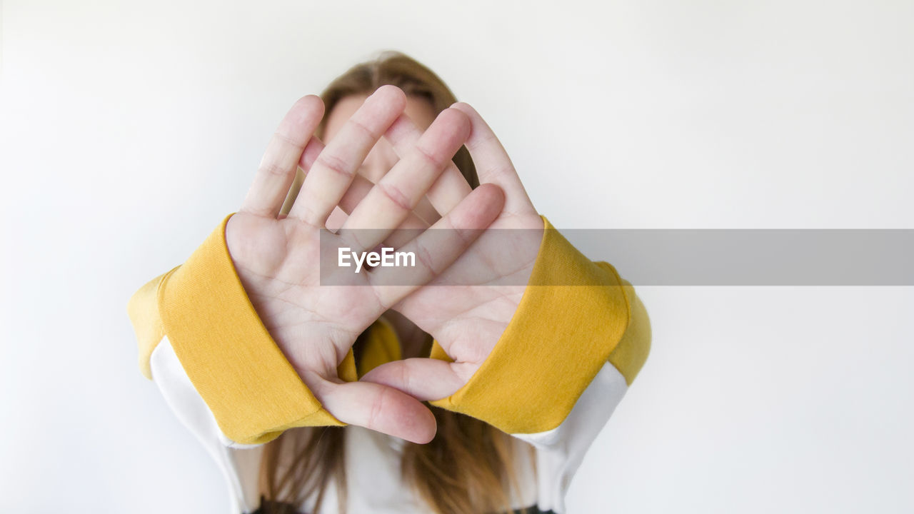 Close-up of woman covering face with hands against white background