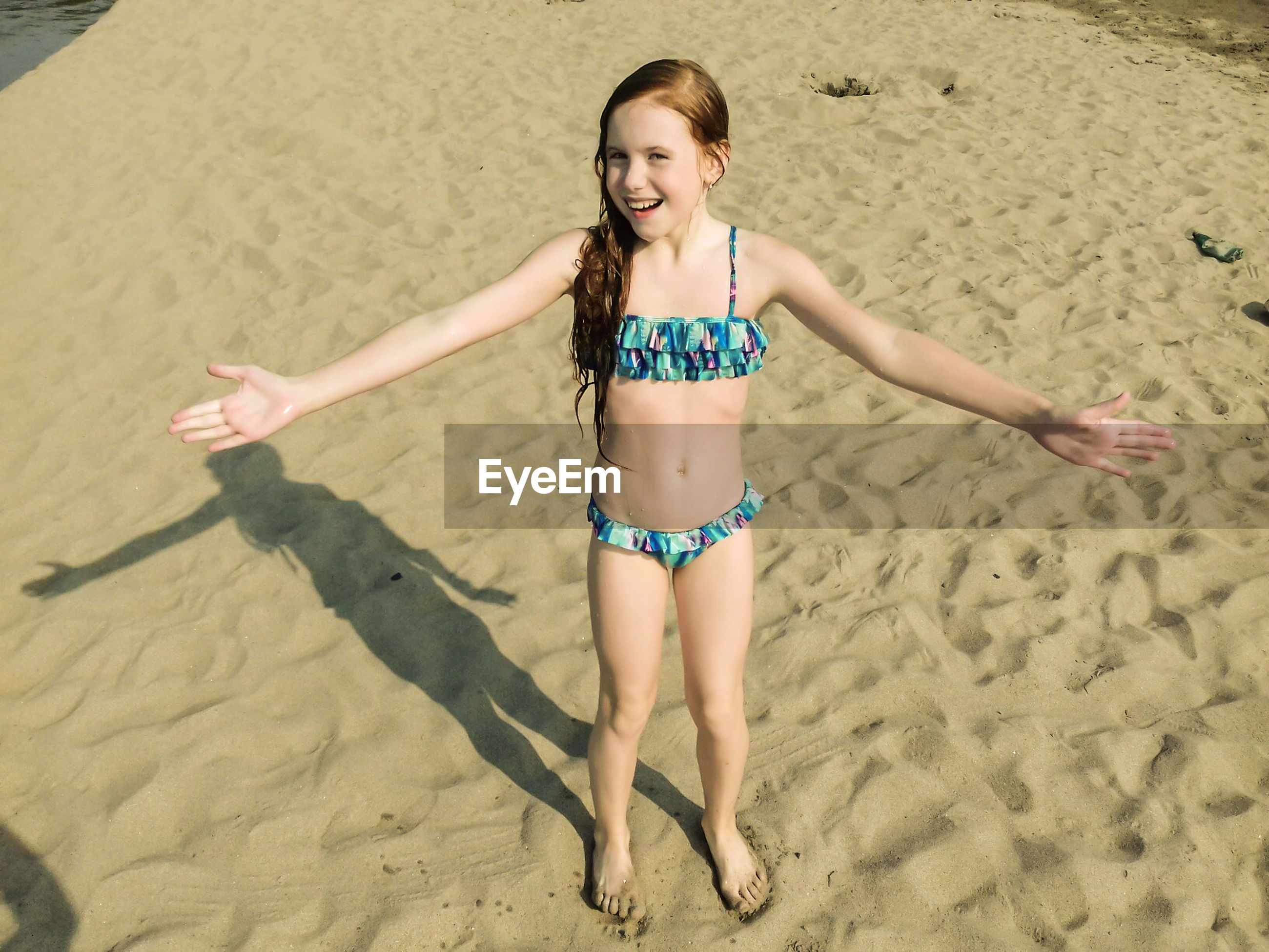 Portrait of happy girl in swimwear with arms outstretched standing at beach