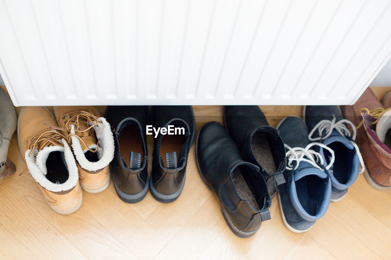 shoe, flooring, indoors, hardwood floor, pair, wood, no people, high angle view, variation, side by side, choice, still life, boot, home interior, wood - material, group of objects, in a row, absence, large group of objects, shoelace, order, menswear, sock, personal accessory, dress shoe