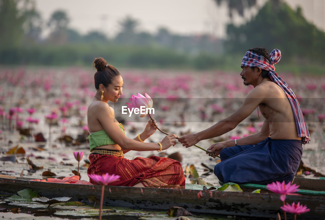 Man Giving Water Lily To Woman Sitting In Boat On Lake