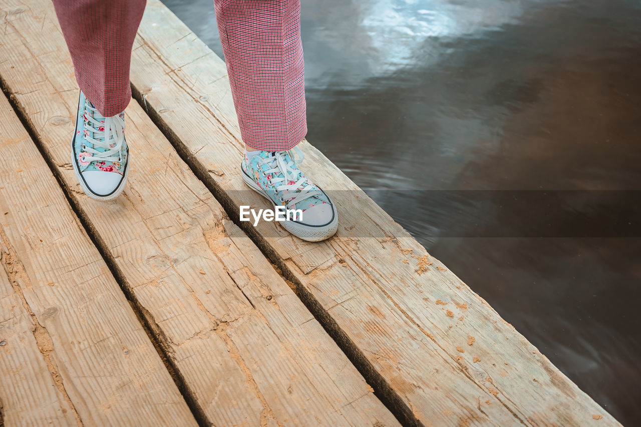 Women's feet walk along the edge of the wooden pier. a girl in sneakers takes steps on the dock