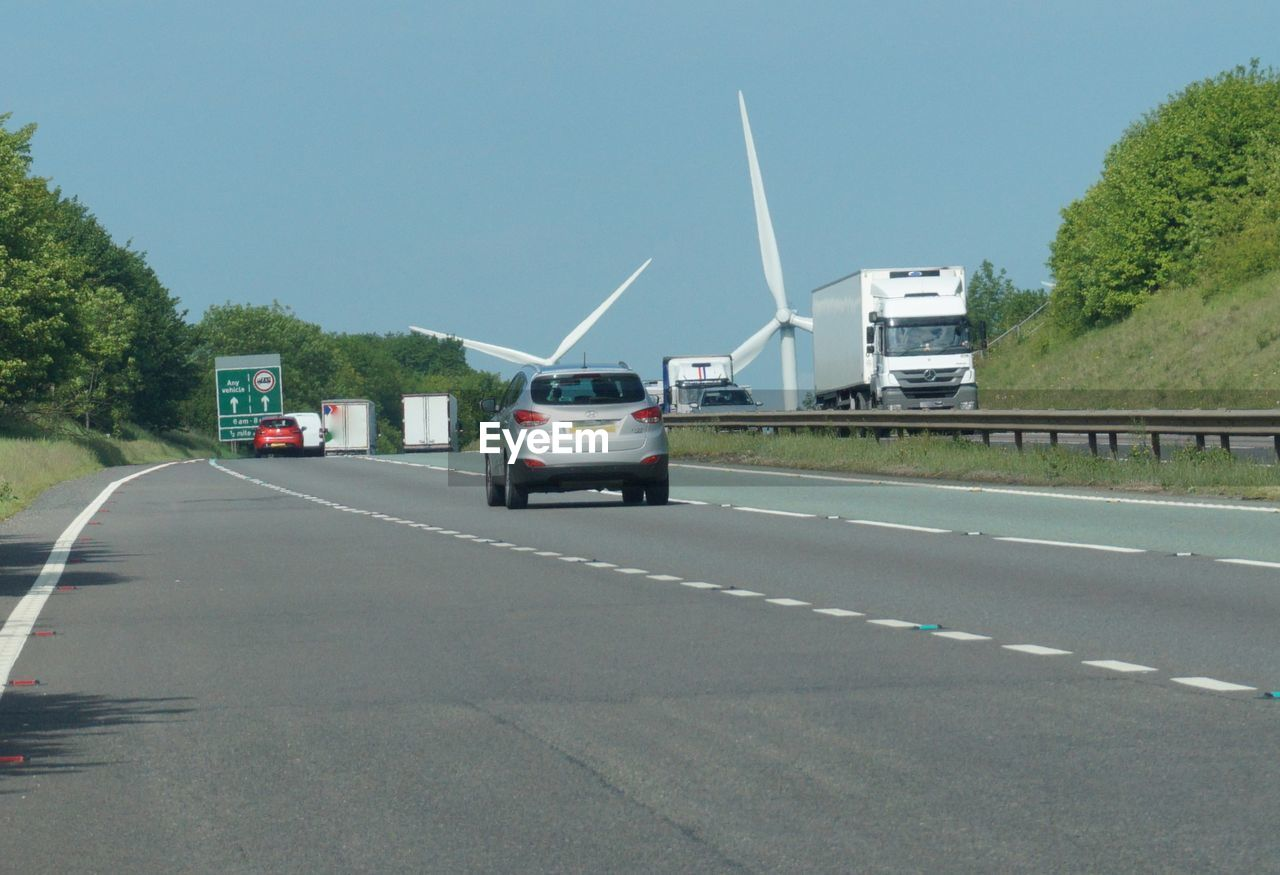Vehicles on highway with wind turbines against sky