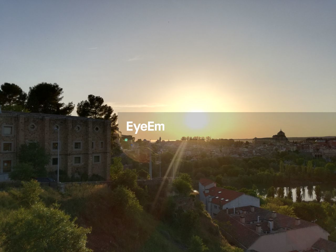 sky, architecture, building exterior, sunset, built structure, building, plant, residential district, sun, nature, tree, sunlight, house, lens flare, no people, city, outdoors, water, high angle view, townscape