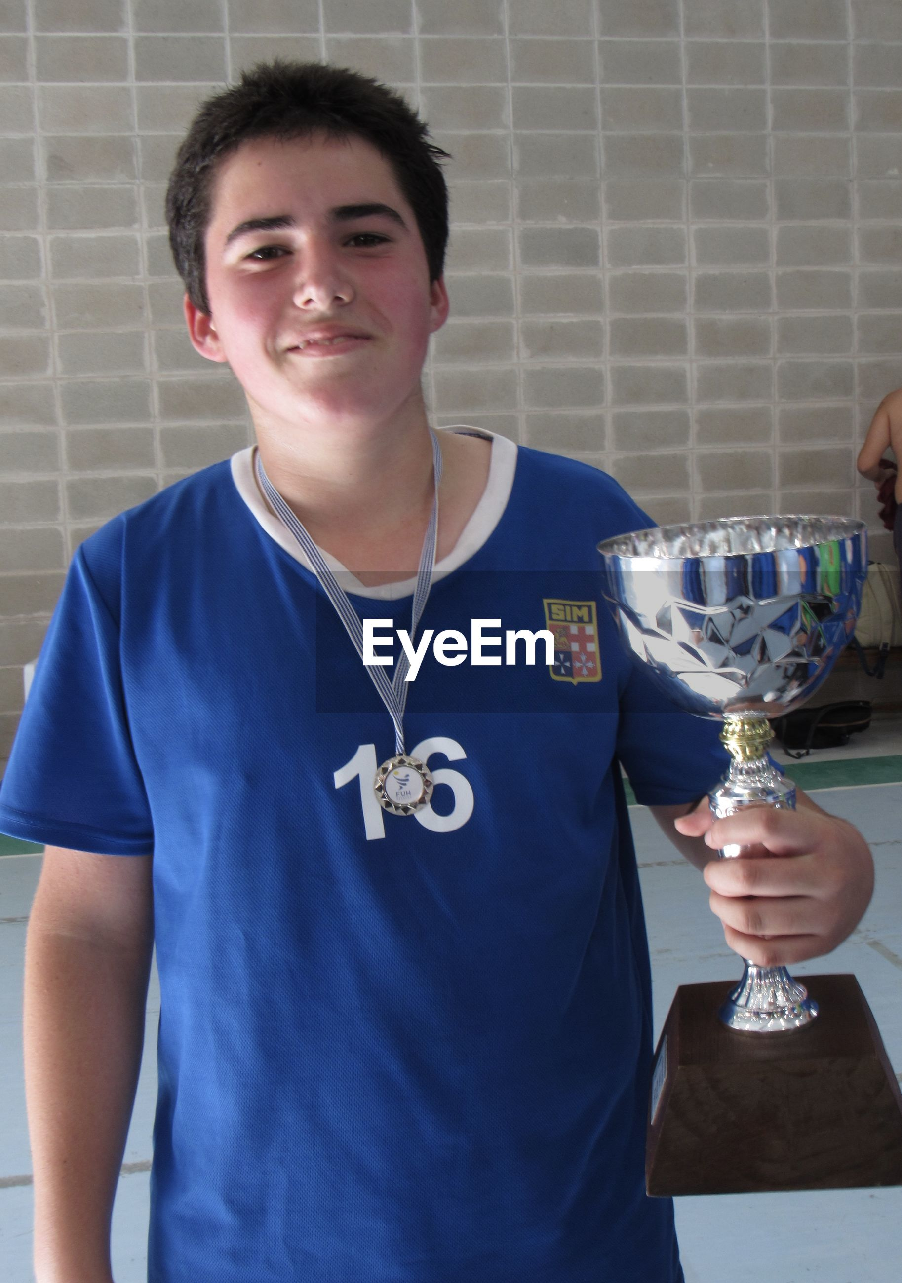 Portrait of smiling boy holding trophy