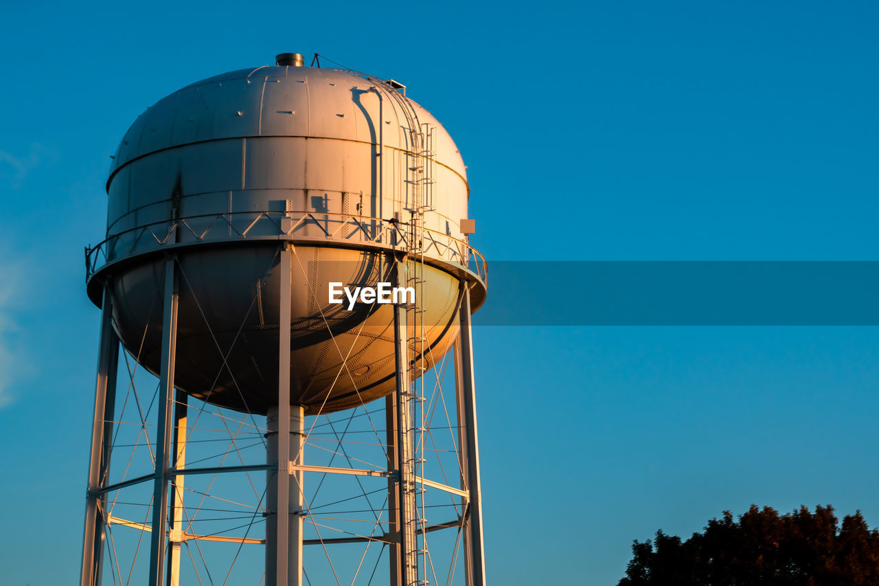 sky, water tower - storage tank, nature, low angle view, built structure, blue, architecture, clear sky, storage tank, no people, building exterior, tree, plant, outdoors, sphere, day, copy space, tower, sunlight, metal, water conservation