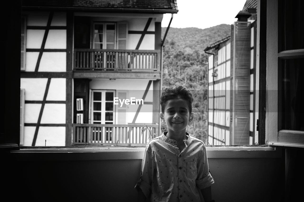 Portrait Of Boy Standing Against Building