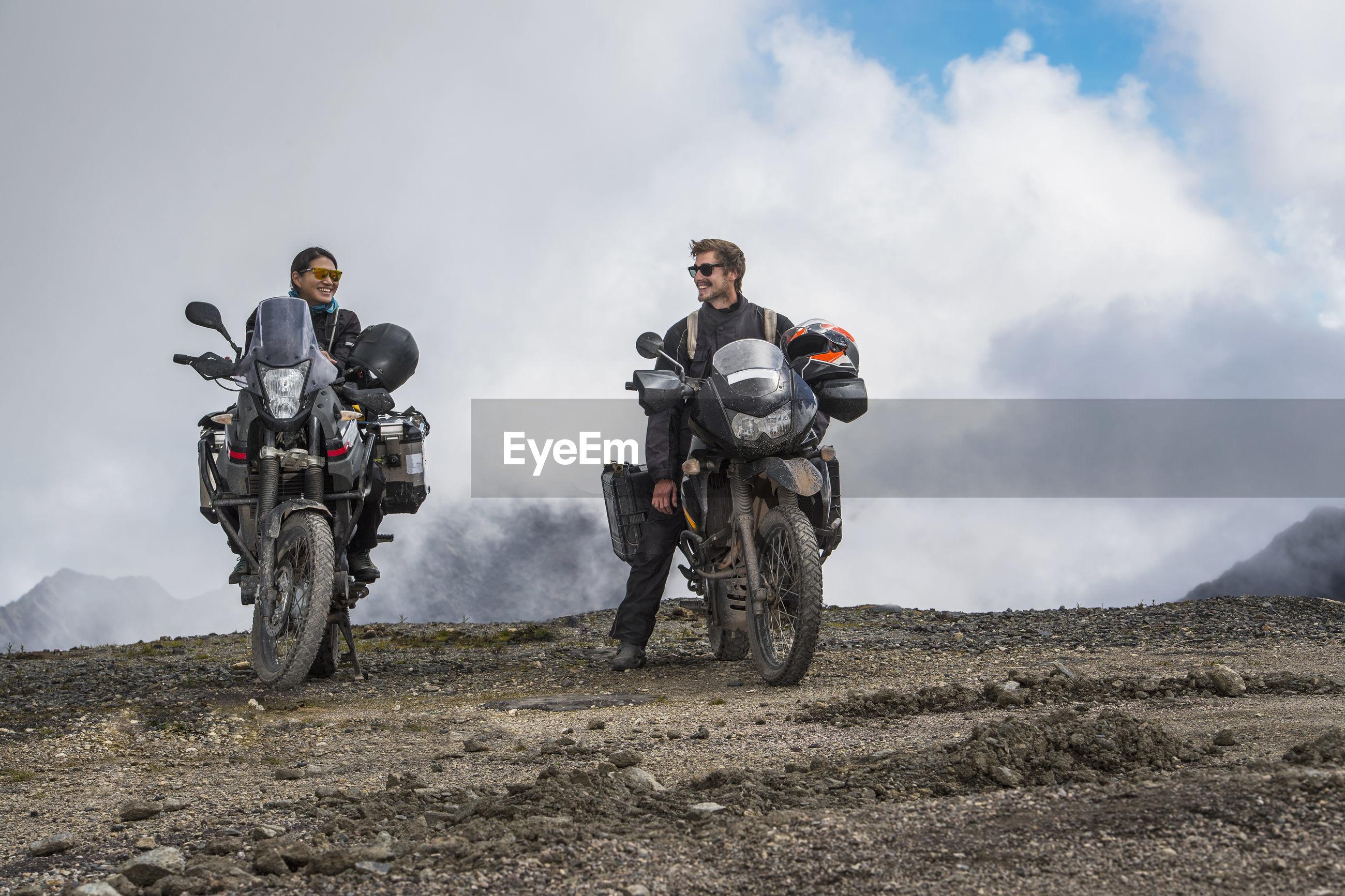 MEN STANDING ON MOUNTAIN AGAINST SKY