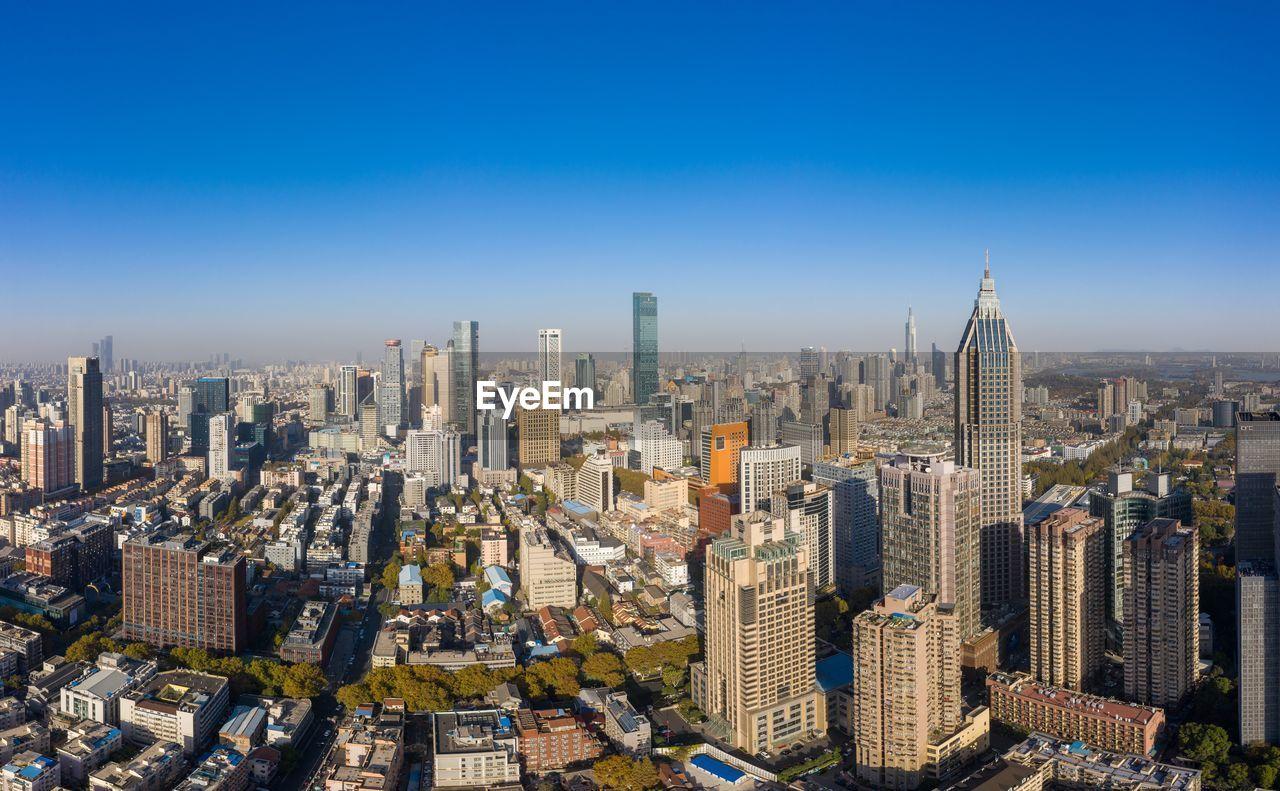 AERIAL VIEW OF CITY BUILDINGS AGAINST BLUE SKY