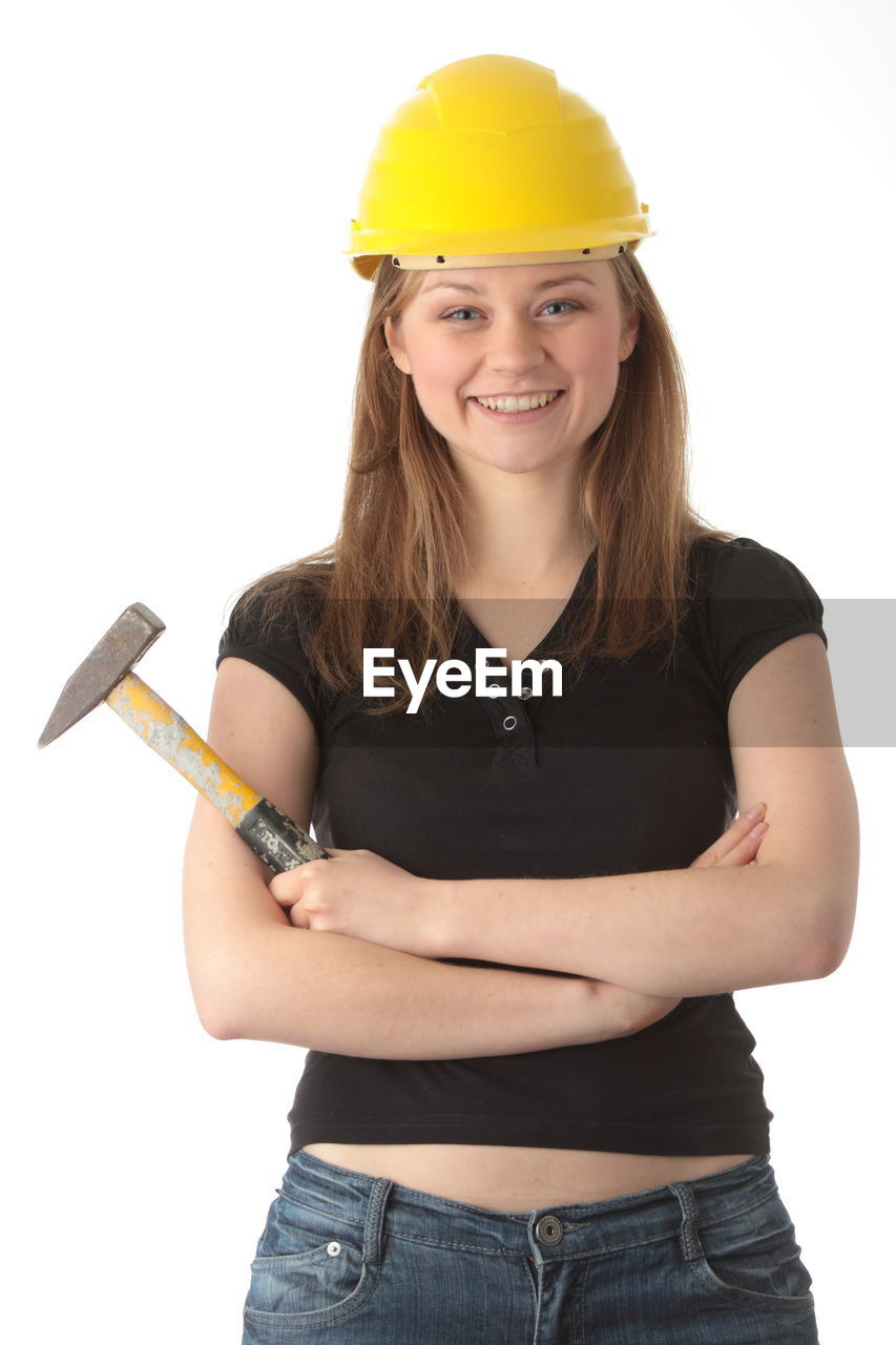 Portrait of happy young woman holding hammer while standing against white background