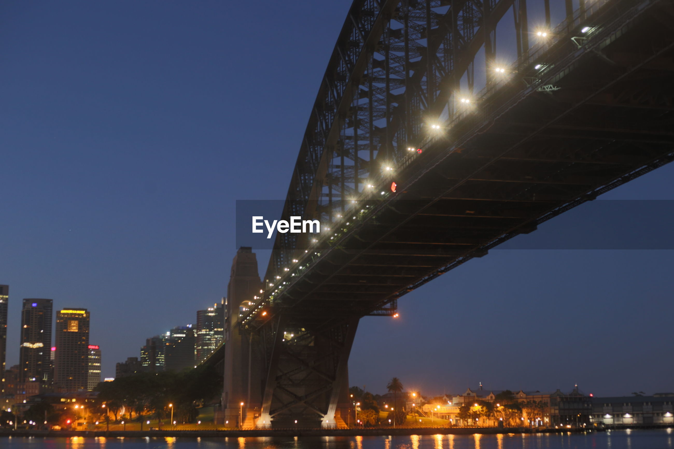 LOW ANGLE VIEW OF ILLUMINATED BRIDGE AGAINST BLUE SKY