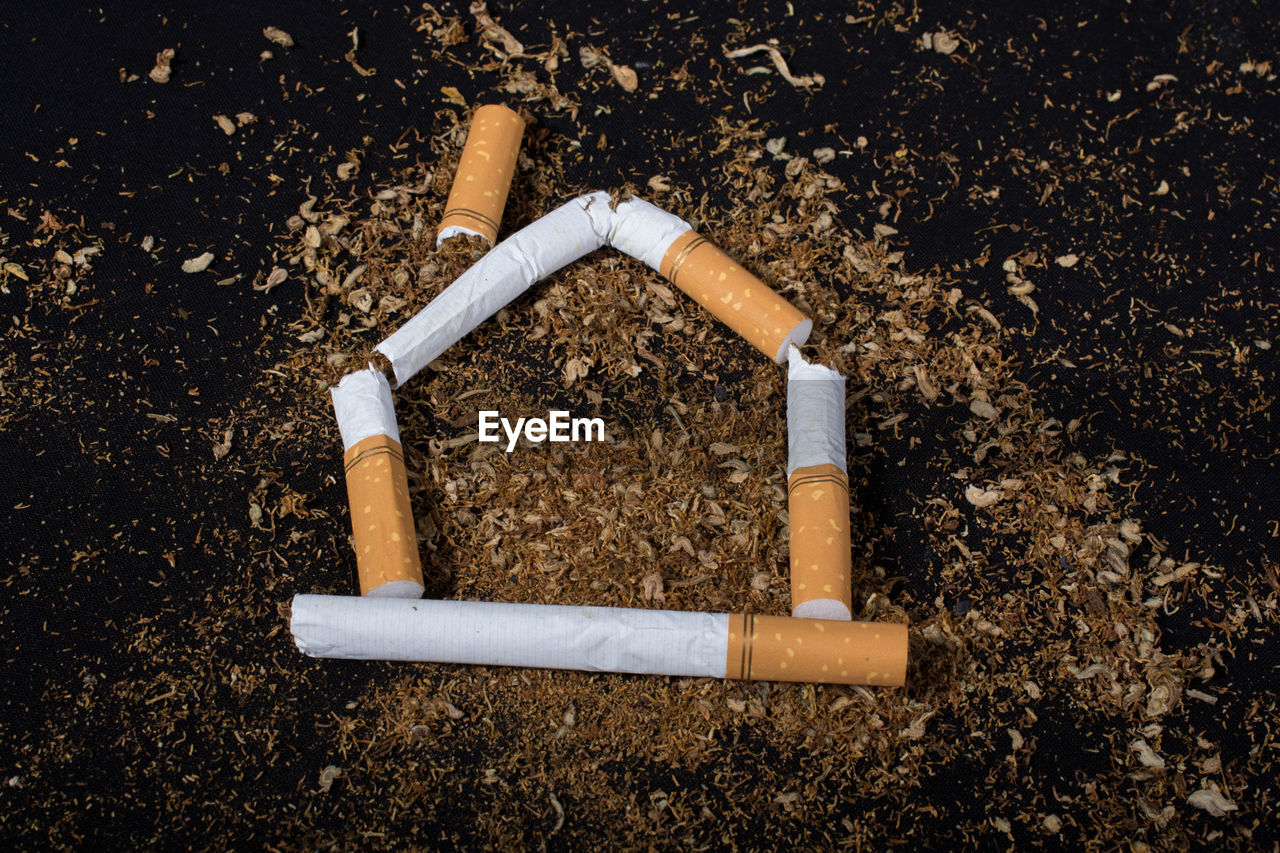 communication, bad habit, cigarette, smoking issues, sign, risk, no people, cigarette butt, warning sign, social issues, tobacco product, ash, burnt, high angle view, day, smoke - physical structure, close-up, outdoors, careless