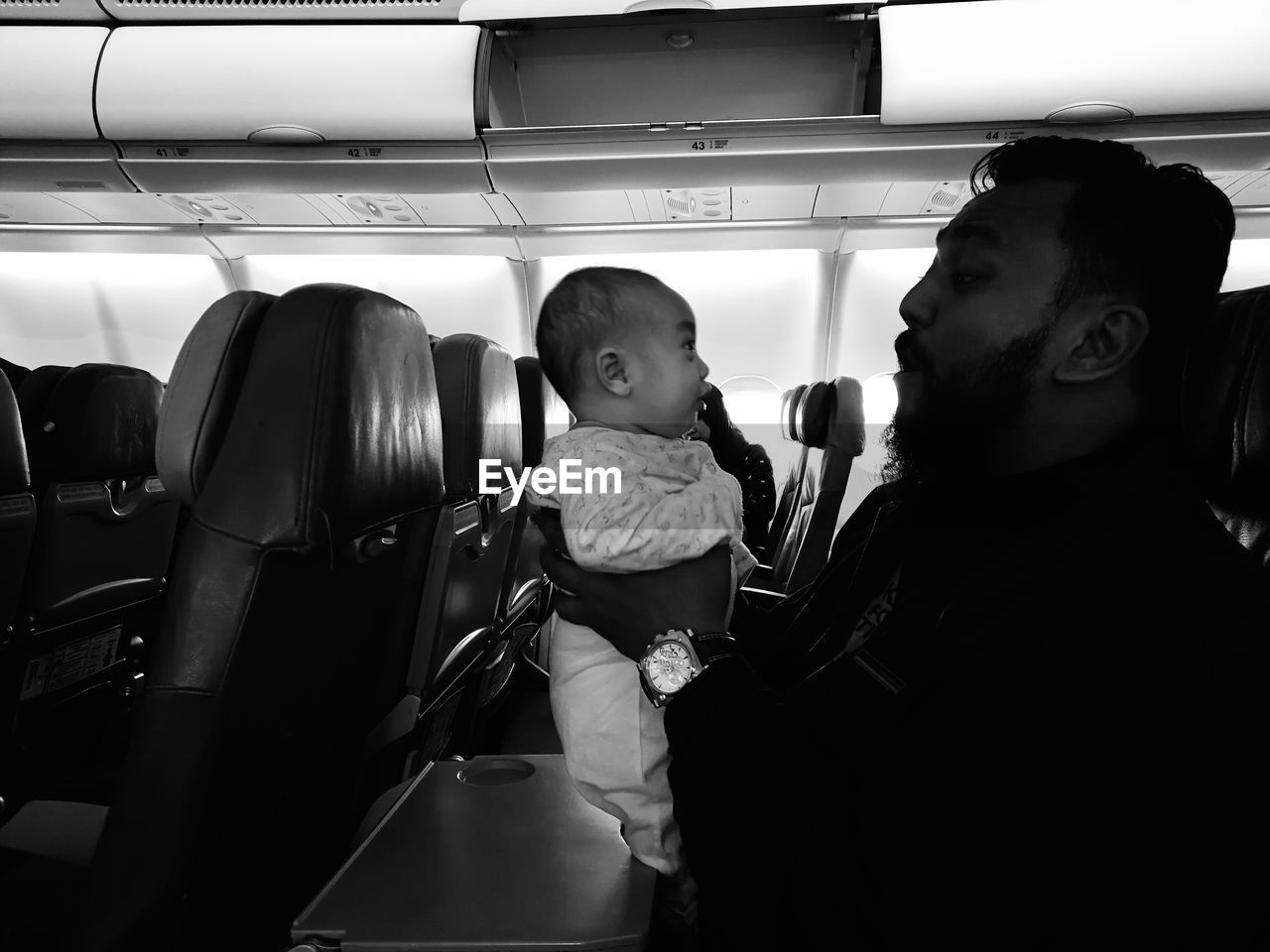 Father Playing With Daughter While Traveling In Airplane