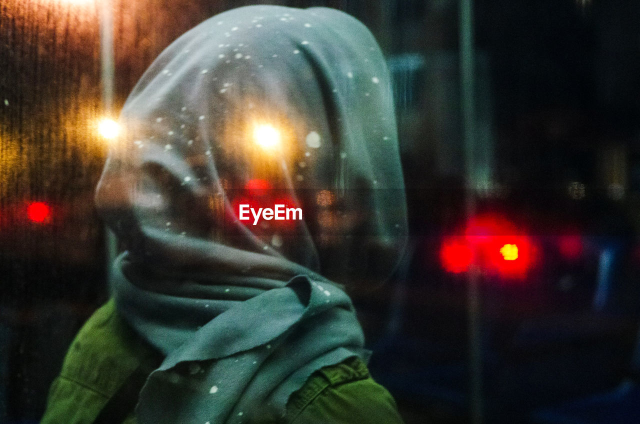 Close-Up Of Woman With Headscarf Seen Through Glass At Night