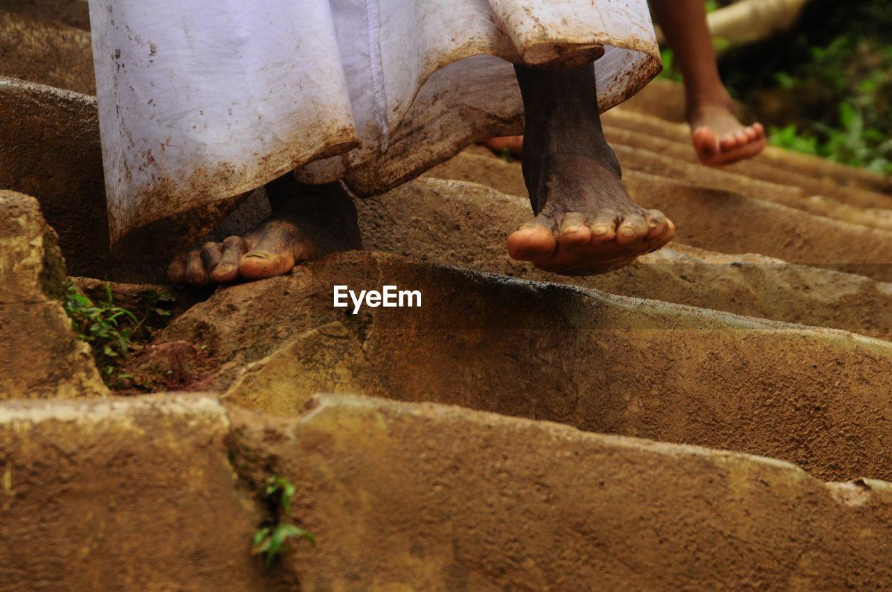 Dirty feet of man on steps