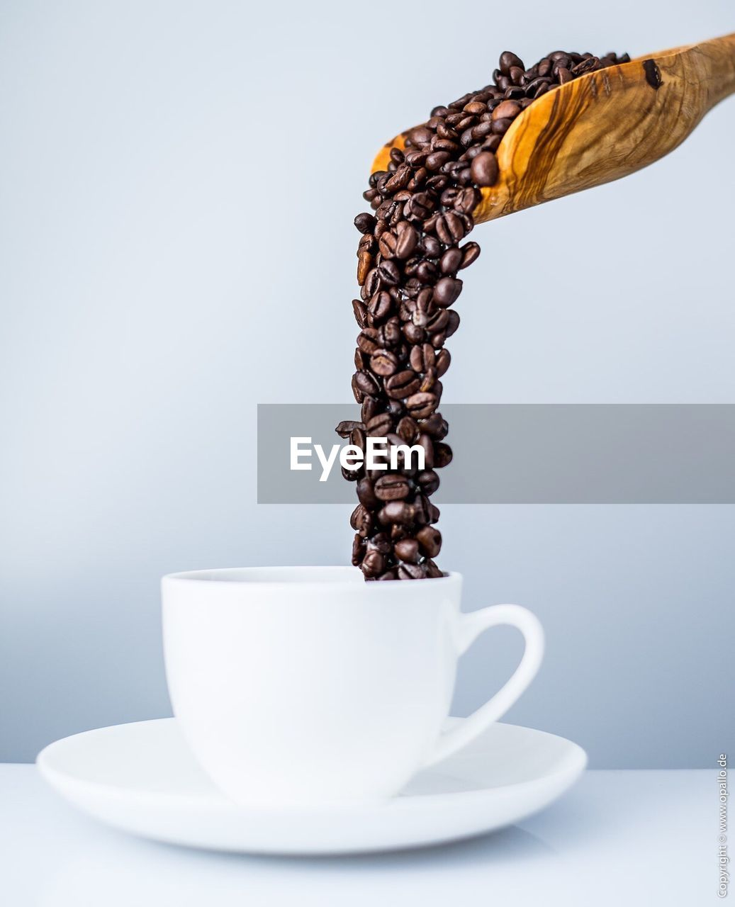 Close-Up Of Spatula Pouring Coffee Beans In Cup Against White Background