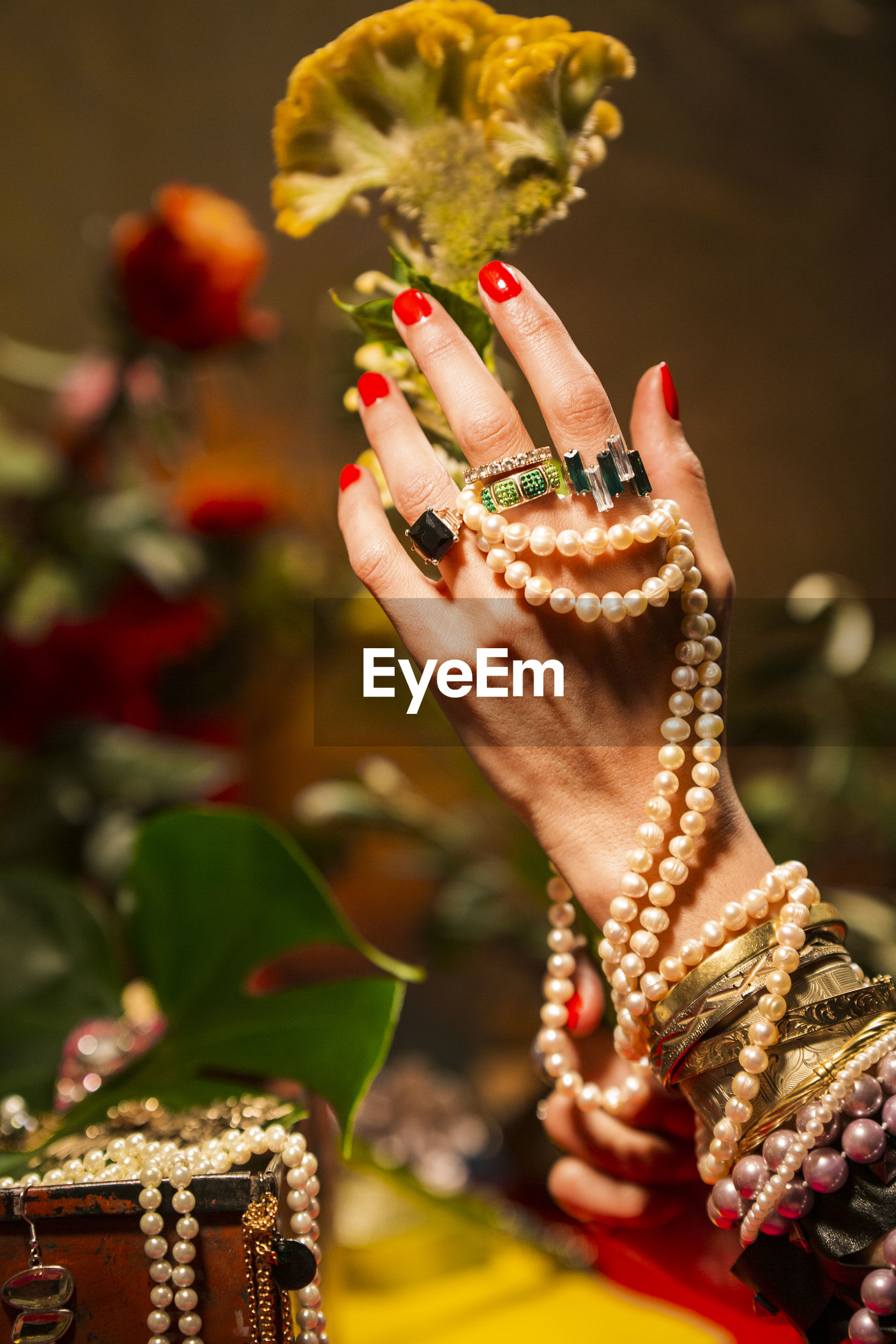Cropped hand of woman with jewelry holding flower