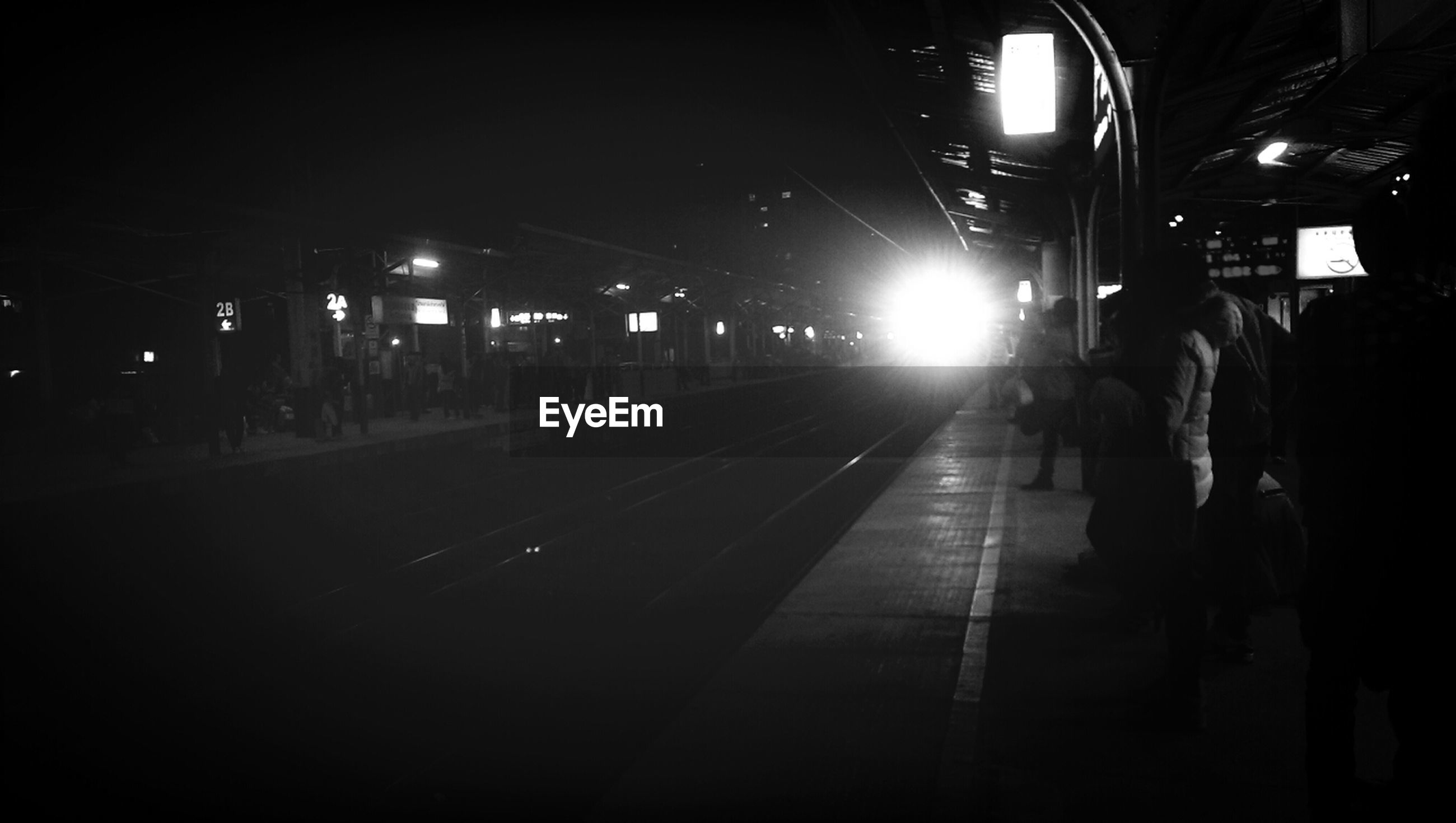 Passengers at platform and light of arriving train