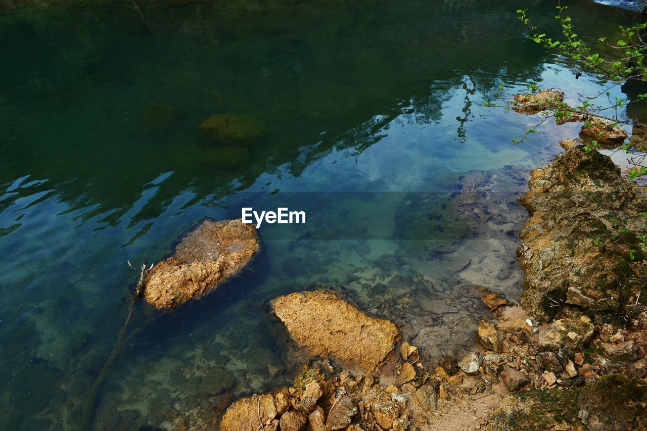 water, rock, high angle view, solid, nature, rock - object, no people, day, lake, beauty in nature, tranquility, reflection, tranquil scene, outdoors, idyllic, scenics - nature, land, transparent, shallow, pollution