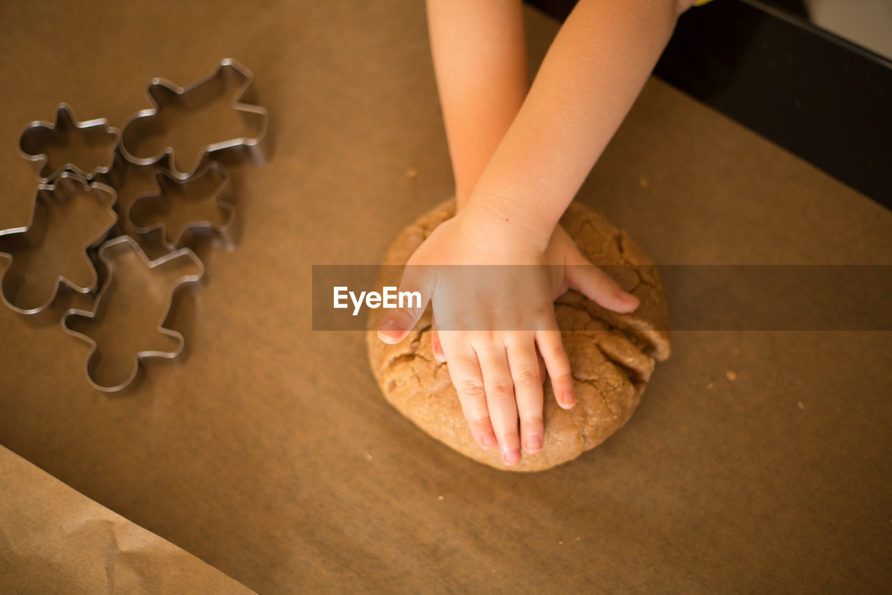 Cropped Hands Of Girl Kneading Dough In Kitchen