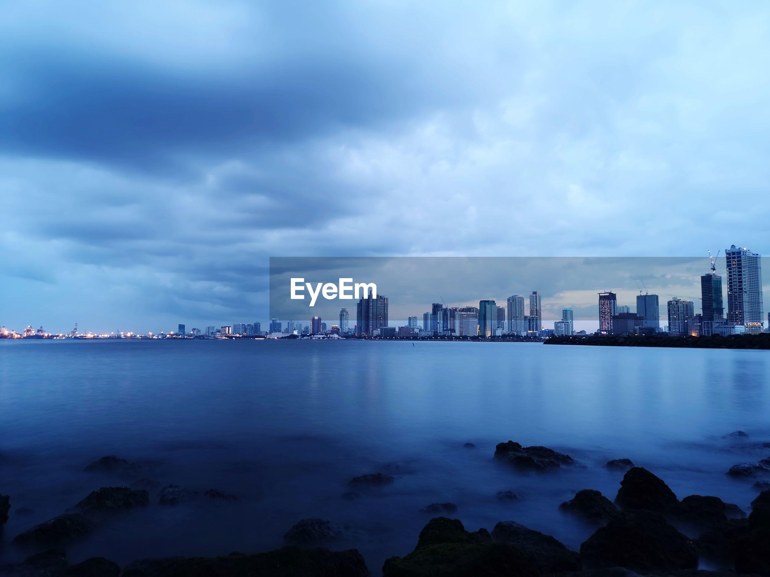 Buildings by sea in city against sky
