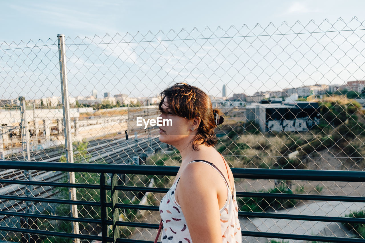 Side View Of Woman Standing By Chainlink Fence In City