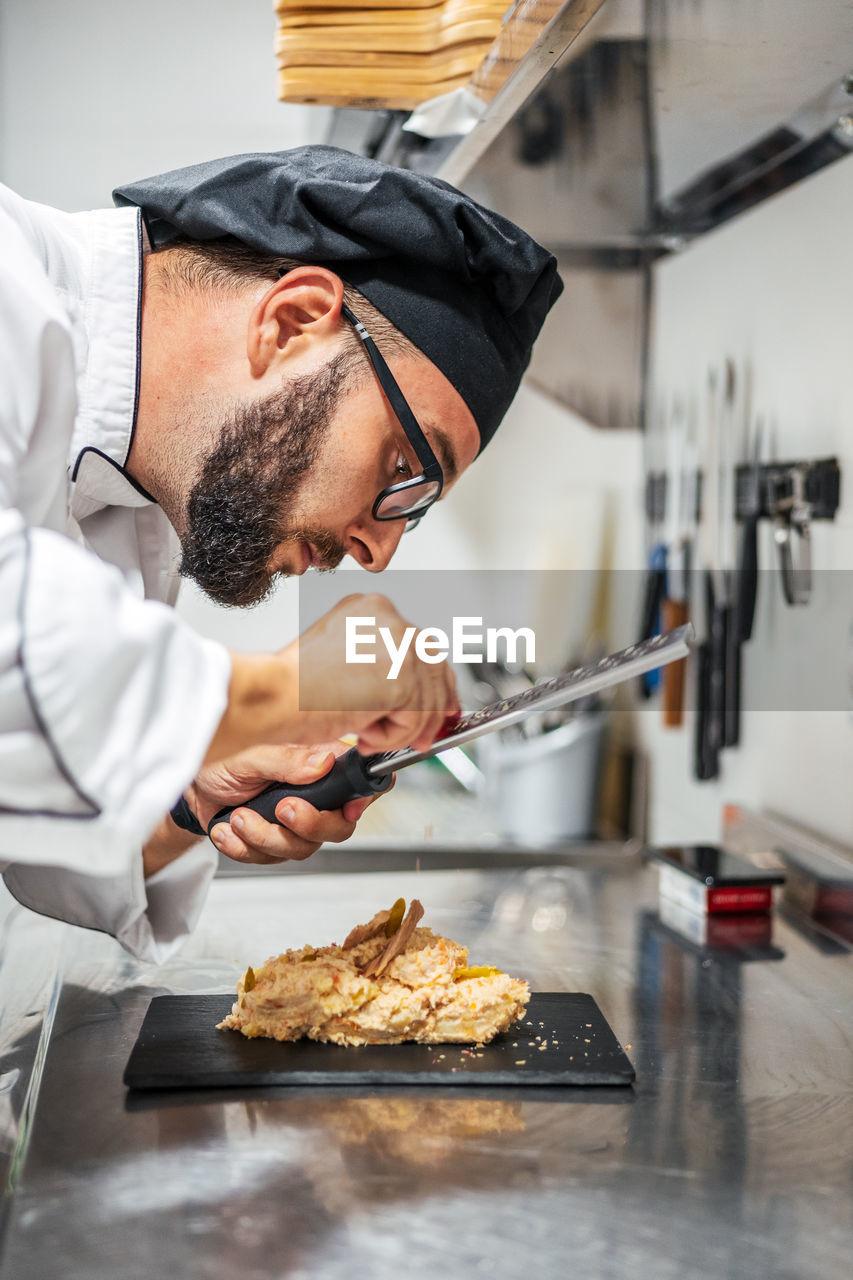 SIDE VIEW OF MAN PREPARING FOOD AT HOME