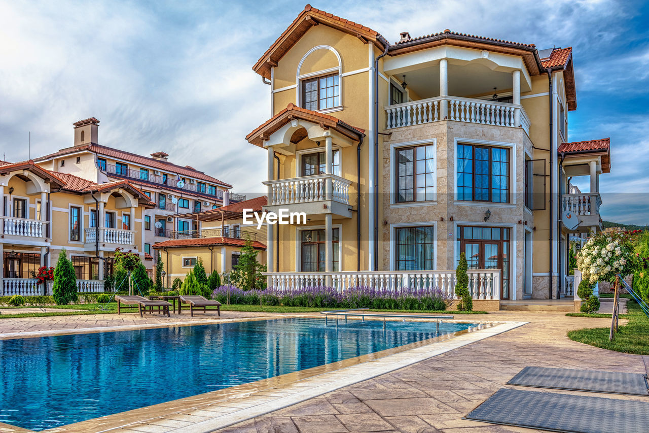 architecture, built structure, building exterior, sky, water, cloud - sky, building, nature, day, swimming pool, no people, pool, outdoors, residential district, house, window, city, tree, reflection, luxury