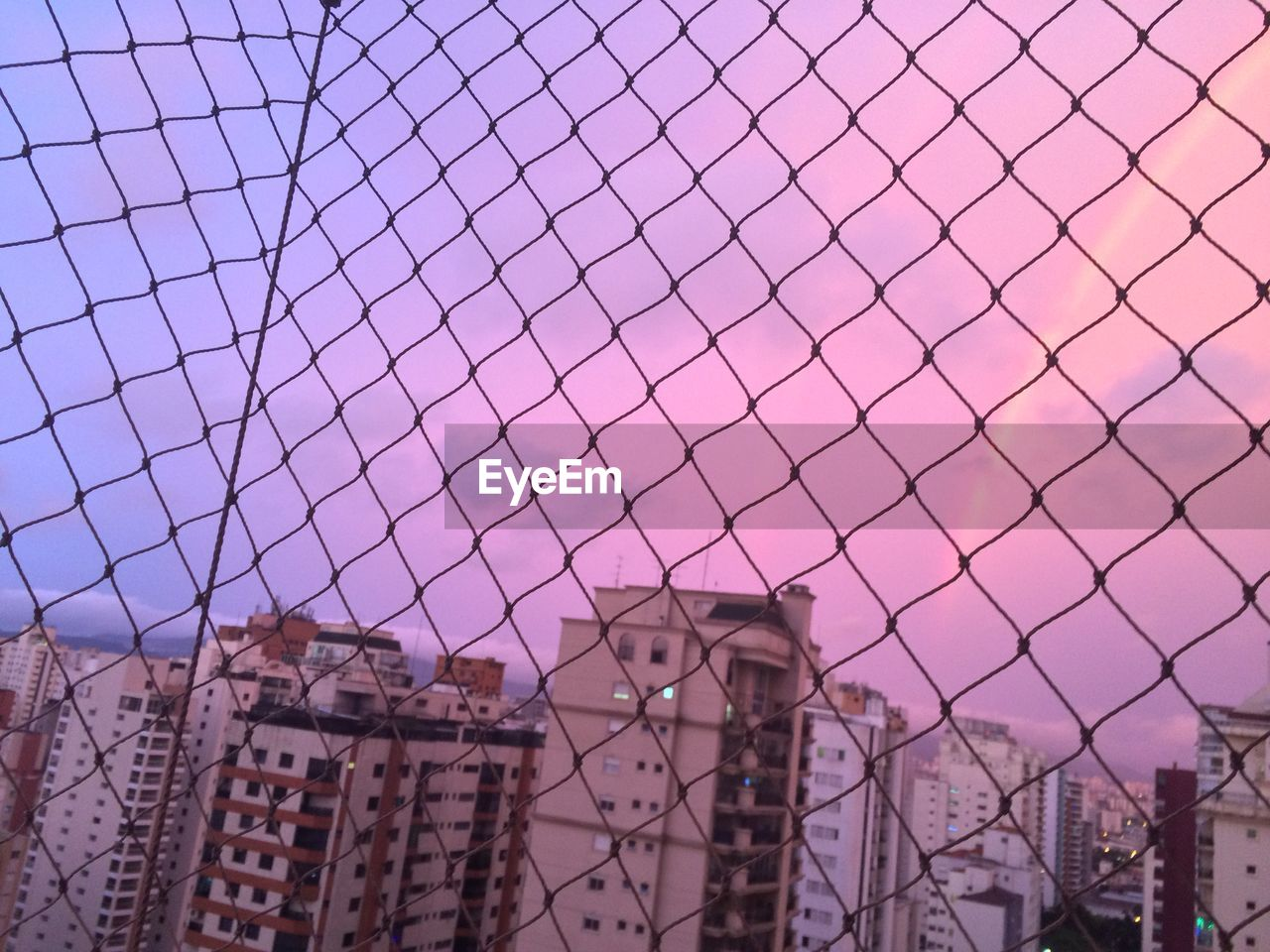 Buildings in city seen through chainlink fence during sunset
