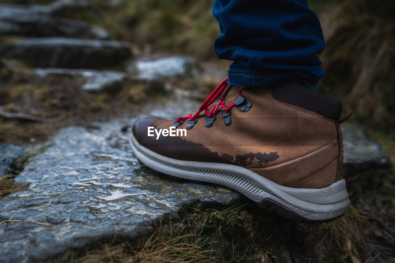 one person, clothing, real people, nature, day, land, focus on foreground, shoe, winter, lifestyles, leisure activity, outdoors, water, unrecognizable person, close-up, field, rock, rock - object, hat, warm clothing