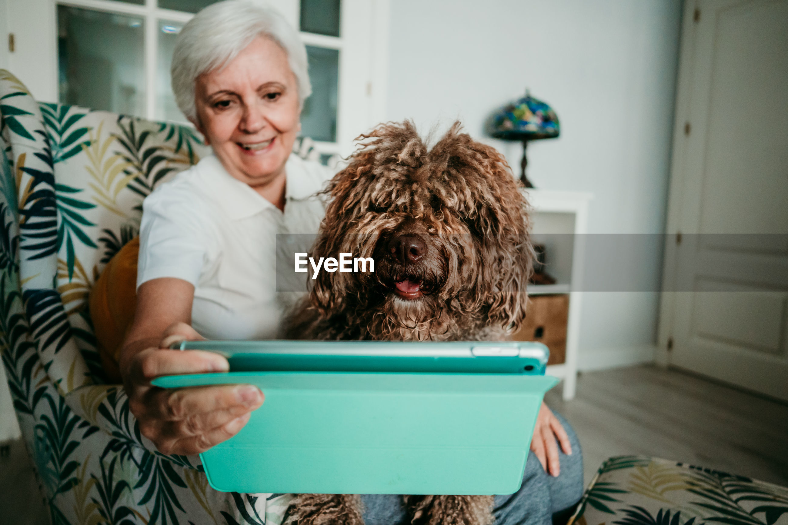 Senior woman with dog using digital tablet