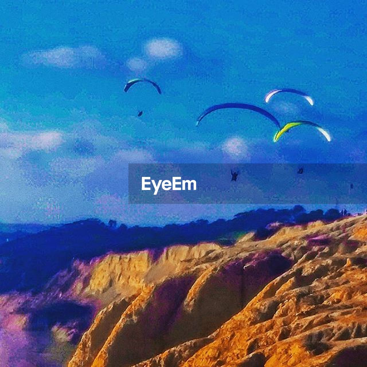flying, mid-air, low angle view, parachute, nature, paragliding, outdoors, extreme sports, multi colored, adventure, beauty in nature, sky, day, scenics, landscape, sport, one person, people, only men