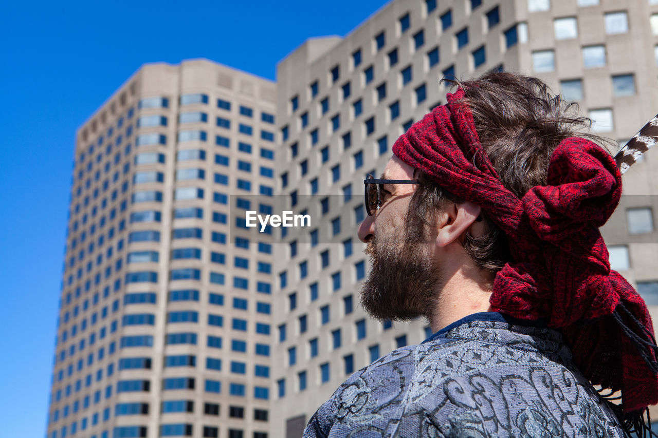 Portrait of man looking at modern office building