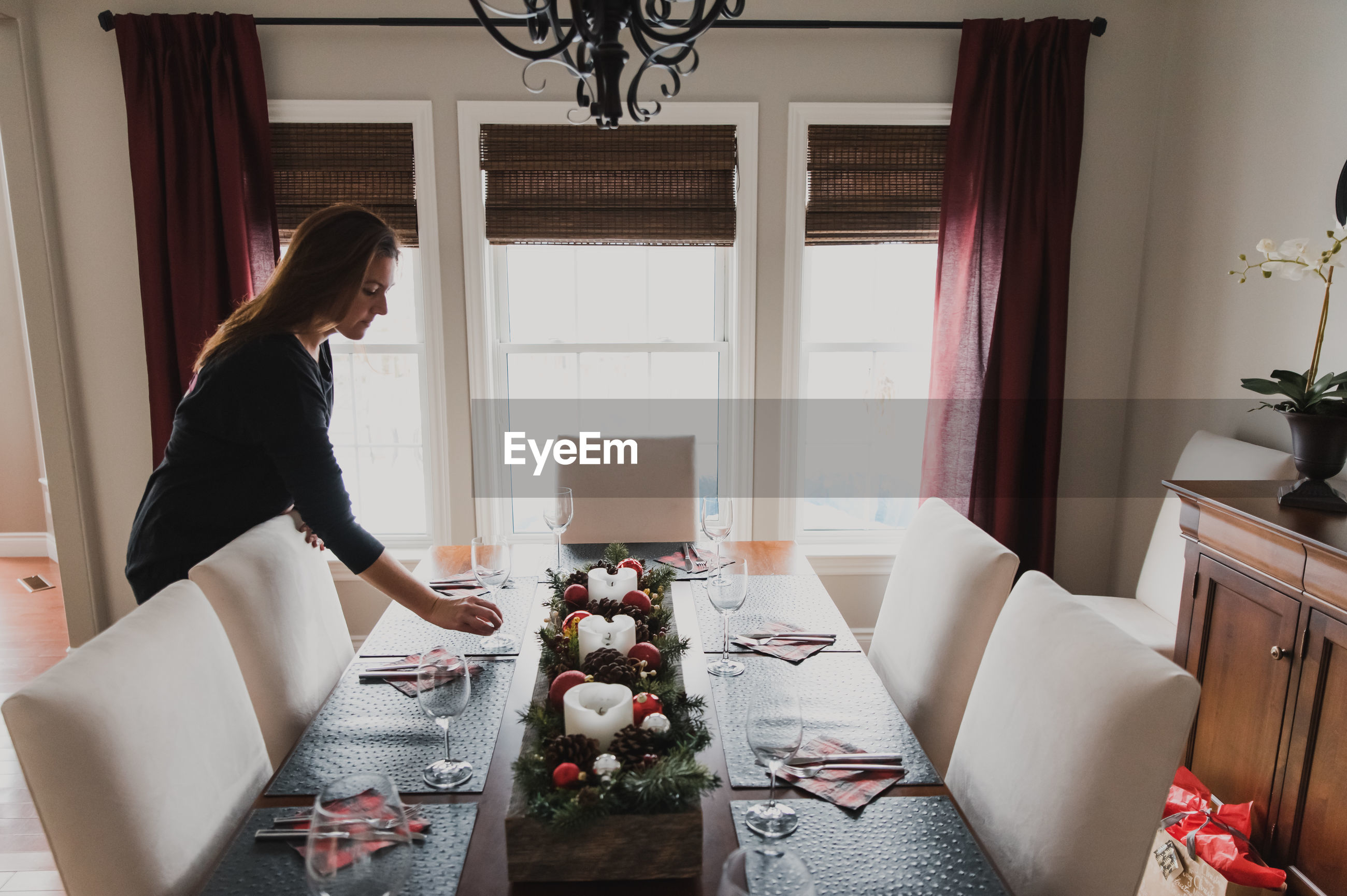 SIDE VIEW OF WOMAN SITTING BY WINDOW AT HOME