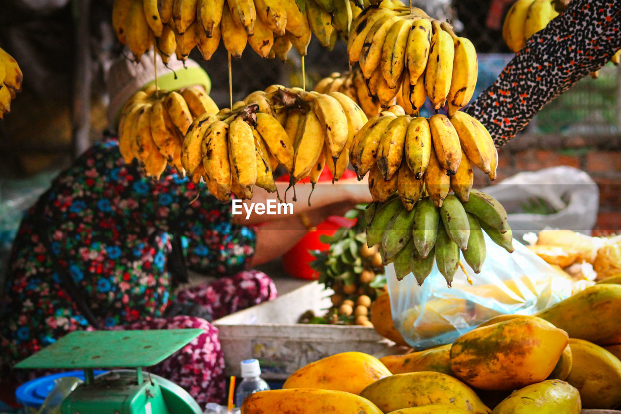 food, food and drink, healthy eating, real people, fruit, market, wellbeing, freshness, market stall, retail, banana, for sale, one person, day, choice, women, small business, yellow, focus on foreground, hand, outdoors, sale