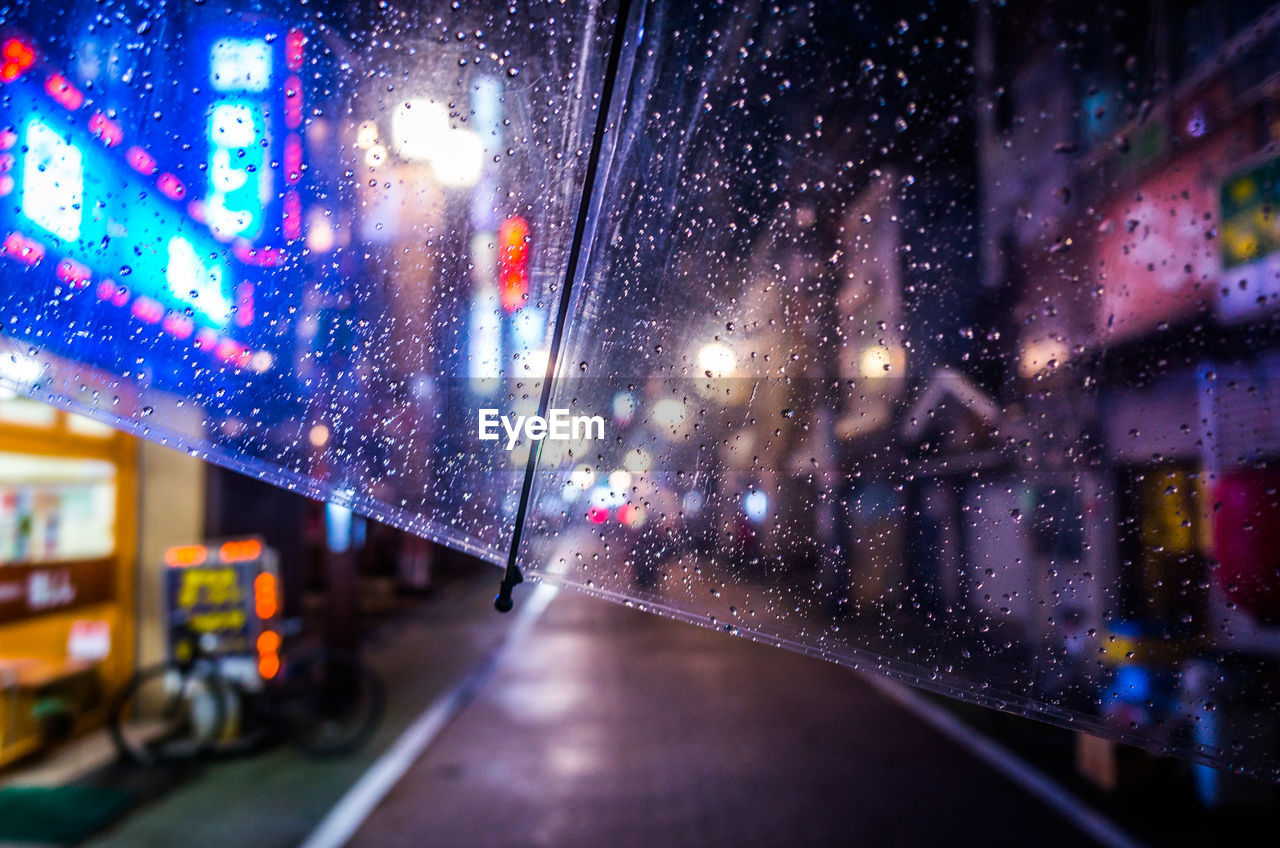 Cropped Image Of Wet Umbrella During Rainy Season On Street At Night