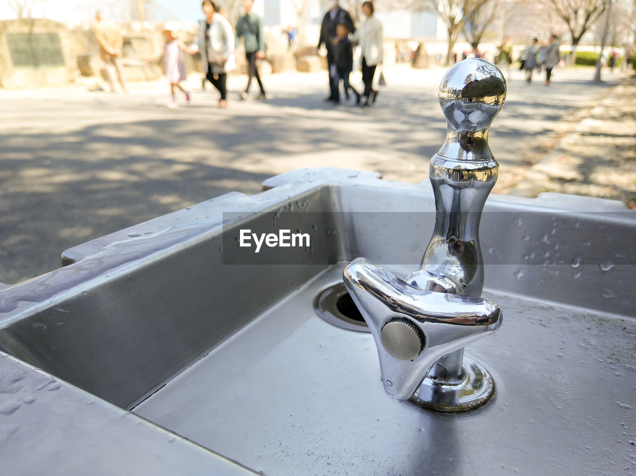 focus on foreground, day, close-up, metal, incidental people, outdoors, city, faucet, street, silver colored, nature, sunlight, still life, road, water, high angle view, table, reflection