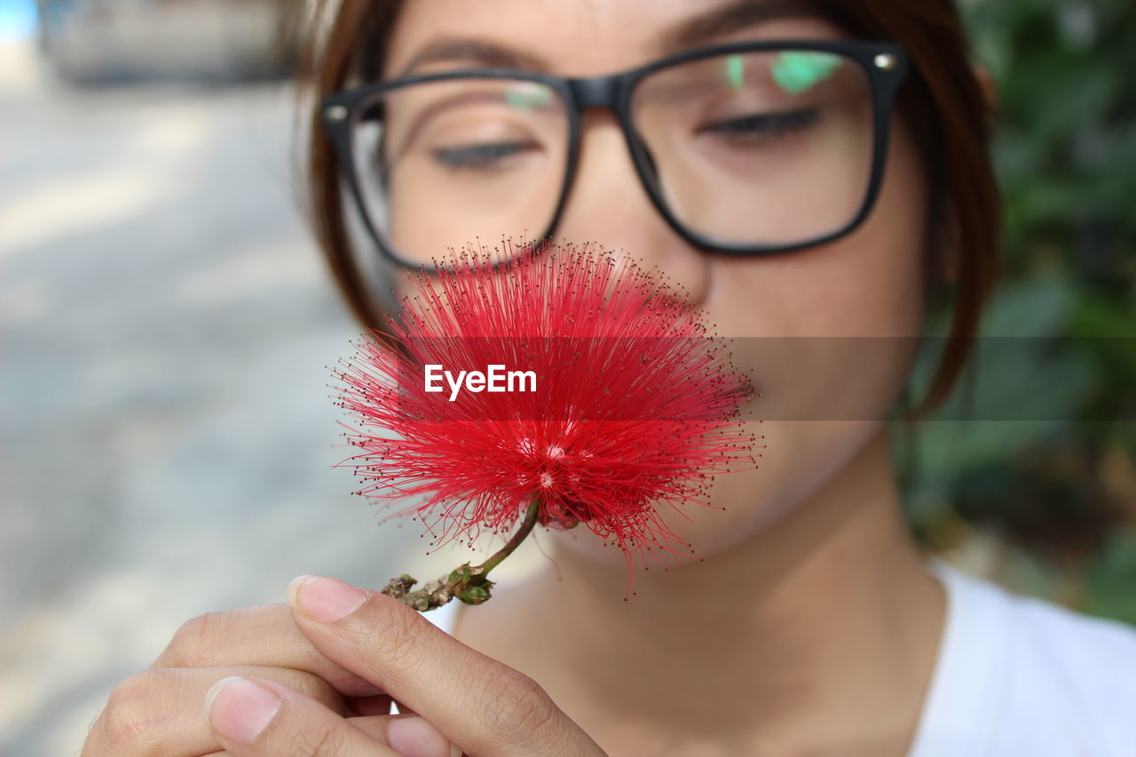 one person, holding, real people, lifestyles, focus on foreground, leisure activity, human hand, human body part, glasses, body part, headshot, young adult, young women, women, close-up, flower, adult, nature, portrait, hand, fashion, outdoors, flower head, finger, human face