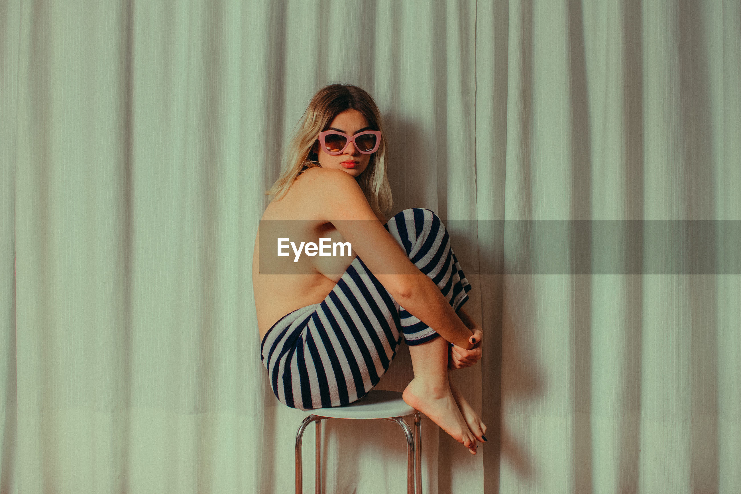 Side view of shirtless young woman wearing sunglasses while sitting on chair by curtain