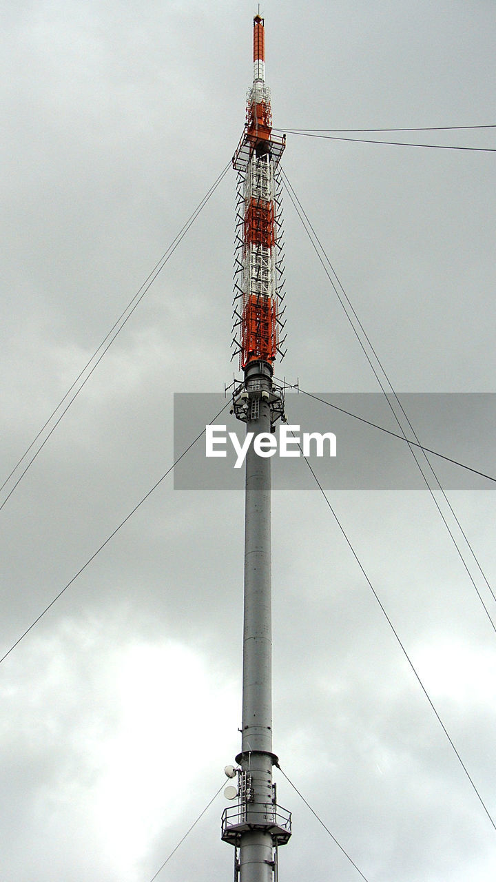 sky, low angle view, cable, technology, electricity, connection, cloud - sky, tall - high, day, architecture, built structure, nature, power line, tower, fuel and power generation, power supply, industry, metal, no people, outdoors, complexity, electrical equipment, global communications