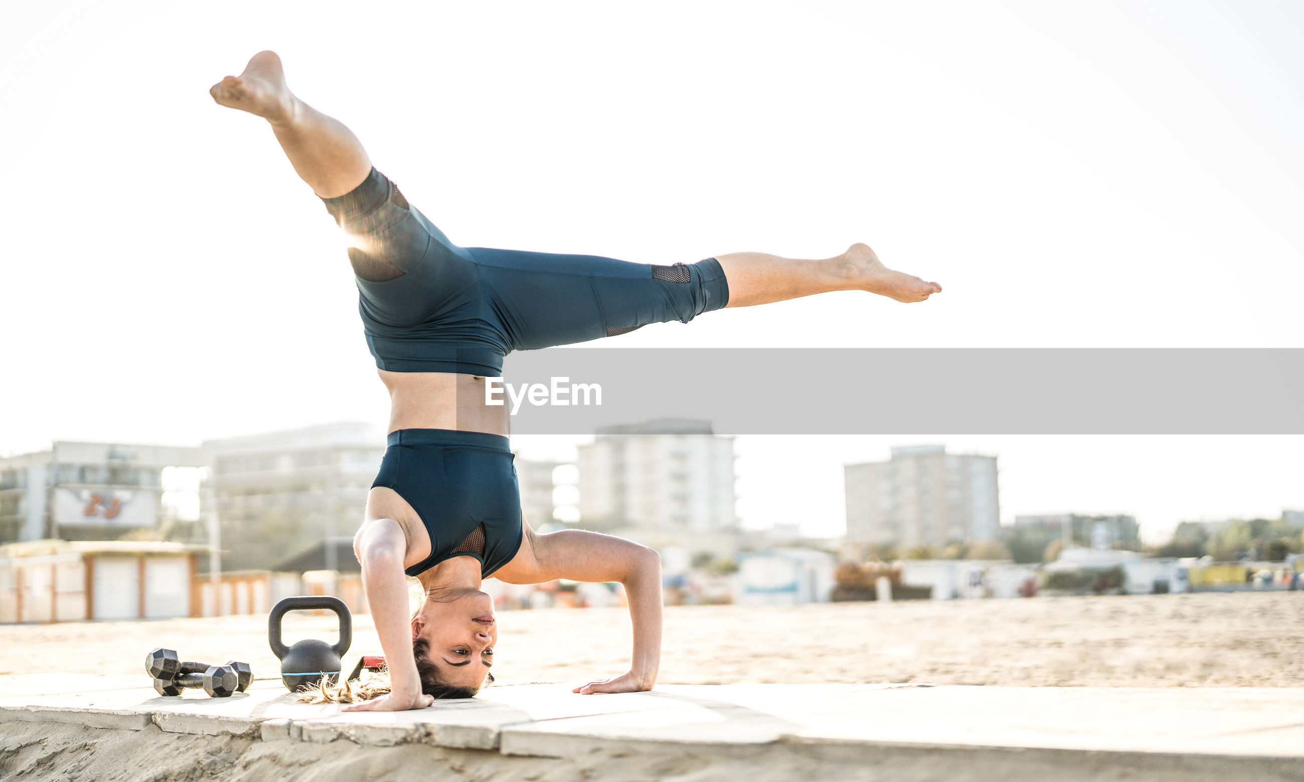 Full length of woman practicing headstand on retaining wall against sky