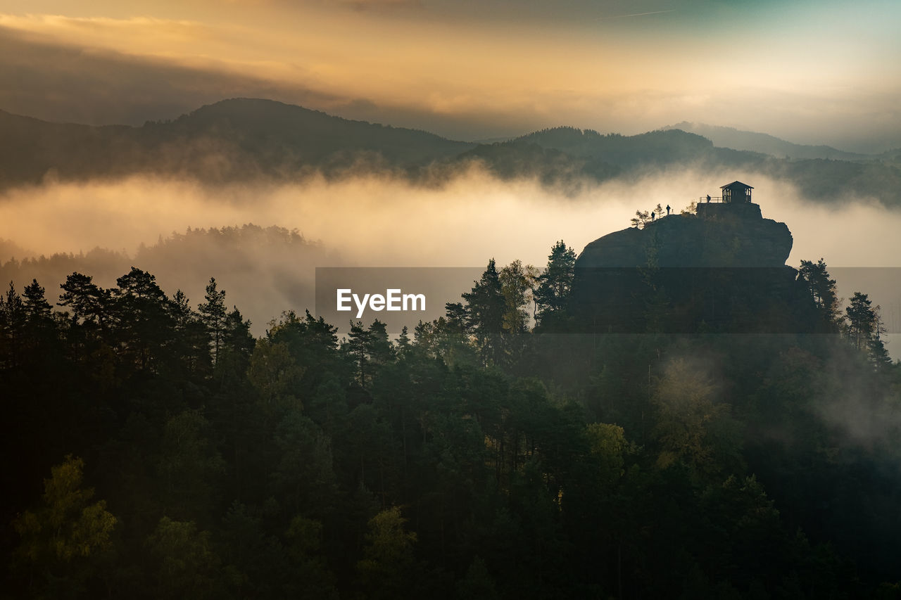 Islands above misty valley, mountain peak with cabin at sunrise. autumn weather with orange mist