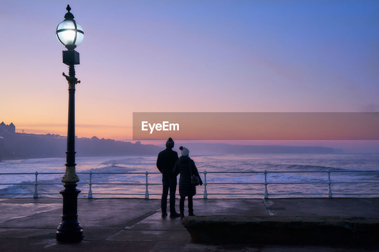 Couple By Sea Against Sky At Sunset