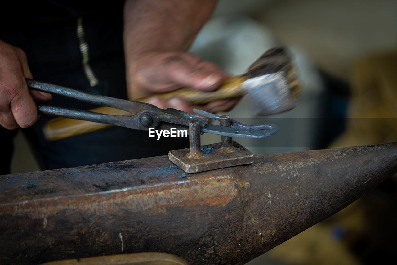 Midsection of man hammering horseshoe on anvil in workshop