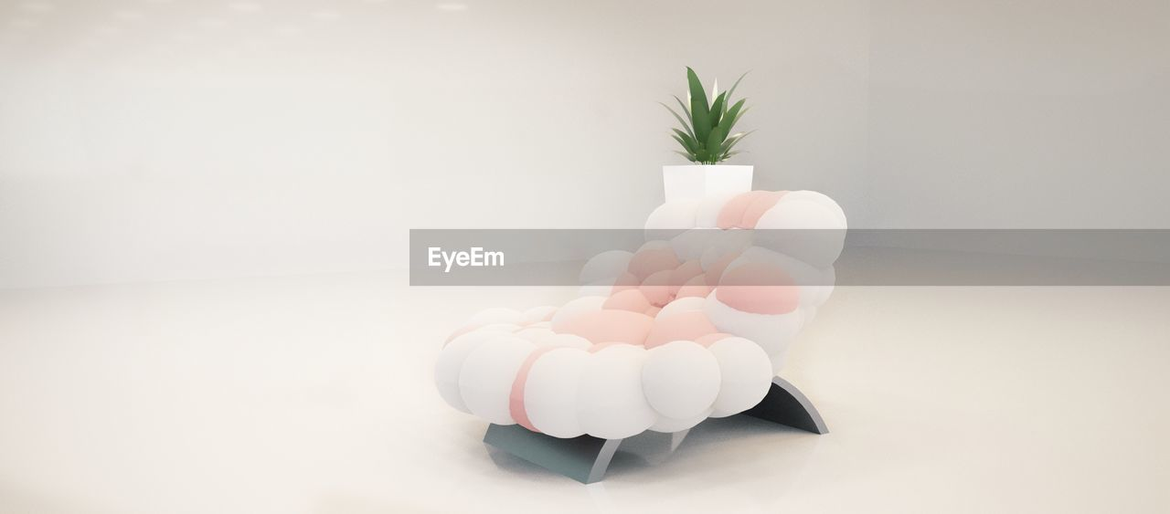 Potted Plant And Empty Chair Against White Background