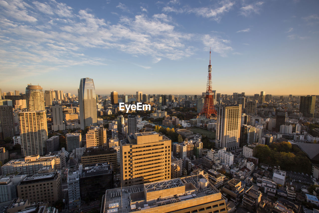 Tokyo Tower Amidst Buildings In City Against Sky During Sunset