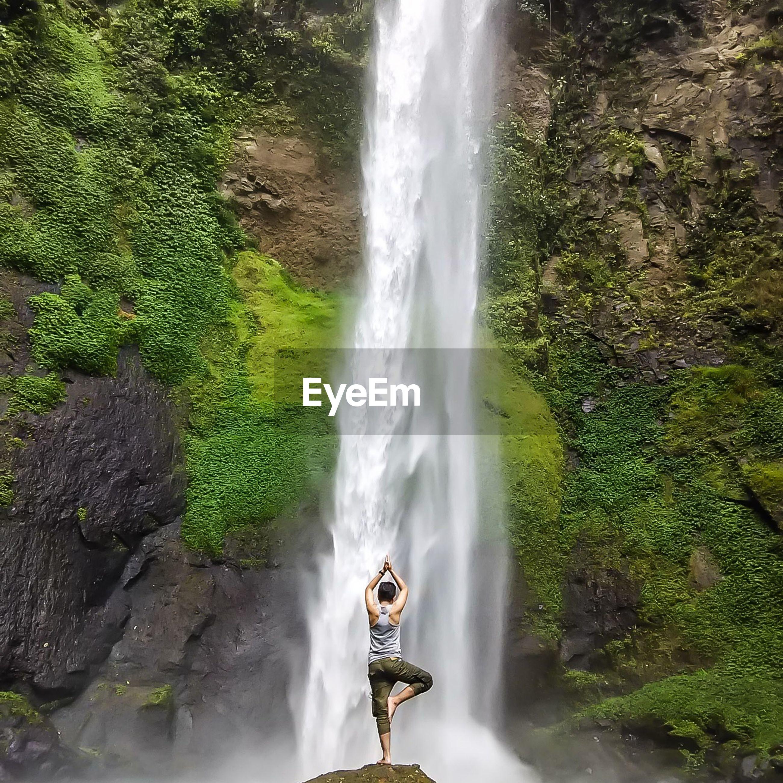 Full length rear view of man performing yoga against waterfall