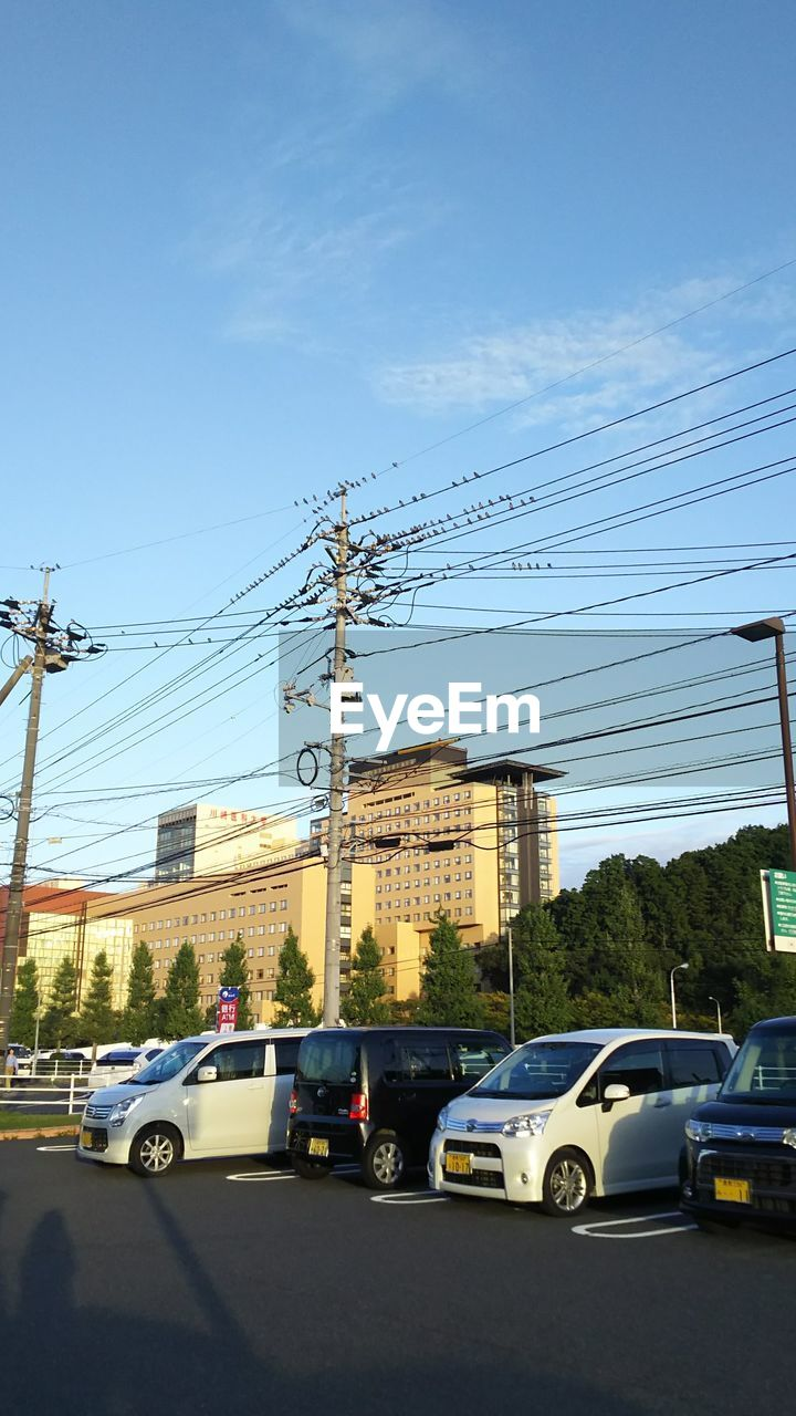 cable, car, electricity, power line, transportation, electricity pylon, power supply, mode of transport, land vehicle, connection, technology, day, built structure, blue, sky, fuel and power generation, road, outdoors, no people, architecture, telephone line, building exterior, city