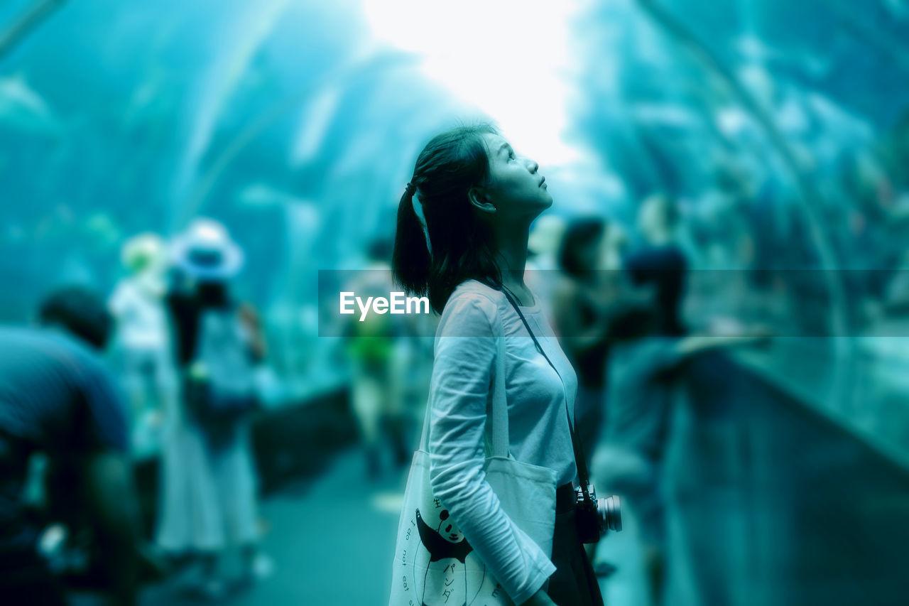 Portrait Of Young Woman In Aquarium