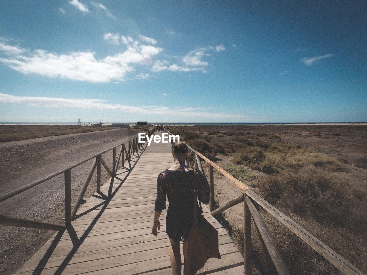 Rear View Of Woman Walking On Boardwalk Against Blue Sky