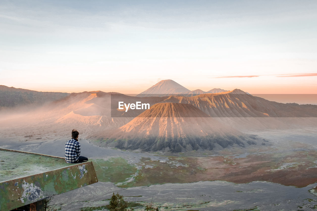 Man Sitting Against Mountain